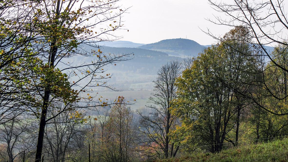 Der 898 Meter hohe Bärenstein und der 1.097 MEter hohe Wirbelstein (Meluzína) im leichten Nebel gehüllt. Foto: Chris Bergau/bergau-media.com