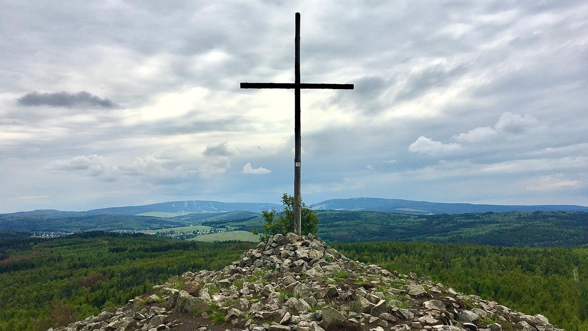 Das Gipfelkreuz auf dem Velký Špičák (Großer Spitzberg). Dahinter rechts der 1.215 Meter hohe Fichtelberg in Deutschland und links der 1.244 Meter hohe Klínovec (Keilberg) in Tschechien. Foto: Chris Bergau/bergau-media.com