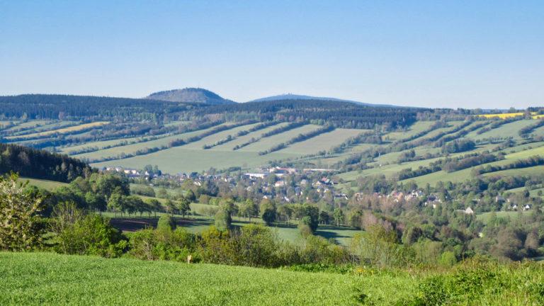 Königswalde, im Hintergrund der 898 Meter hohe Bärensteiner Berg (l.) und der 1.215 Meter hohe Fichtelberg. Foto: Chris Bergau/bergau-media.com